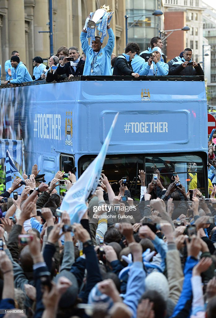 Manchester City captain Vincent Kompany (C) hows off the Barclays Premier League trophy in front of thousands of fans during their victory parade around the streets of Manchester on May 14, 2012 in Manchester, England.