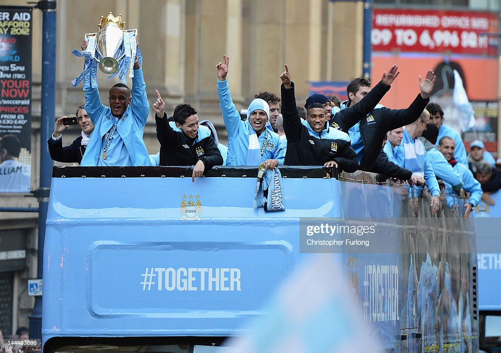 Manchester City captain Vincent Kompany (2ndL) shows off the Barclays Premier League trophy with team mates in front of thousands of fans during their victory parade around the streets of Manchester on May 14, 2012 in Manchester, England.