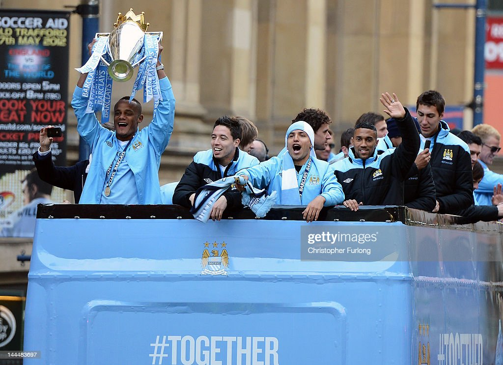 Manchester City captain Vincent Kompany (L) shows off the Barclays Premier League trophy with team mates in front of thousands of fans during their victory parade around the streets of Manchester on May 14, 2012 in Manchester, England.