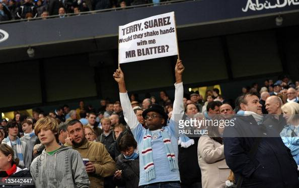 A Manchester City fan displays a banner with a message for FIFA President Sepp Blatter regarding his handling of recent allegations of racism in...