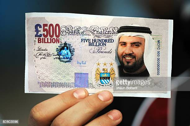 Manchester City fan holds a fake British Pound note with the face of Dr Sulaiman Al Fahim during the Barclays Premier League match between Manchester...
