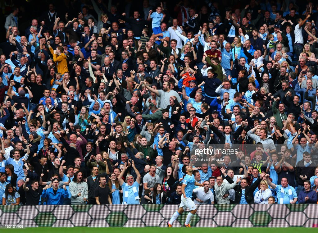 Manchester City fans celebrate after Sergio Aguero of Manchester City scores their team's second goal during the Barclays Premier League match between Manchester City and Everton at Etihad Stadium on October 5, 2013 in Manchester, England.
