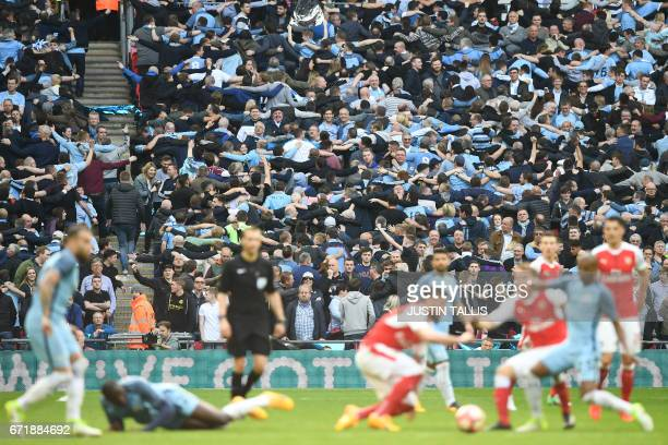 Manchester City fans celebrate Manchester City's Argentinian striker Sergio Aguero's opening goal during the FA Cup semifinal football match between...