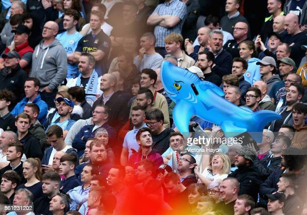 Manchester City fans hold up a blow up shark for Benjamin Mendy prior to the Premier League match between Manchester City and Stoke City at Etihad...