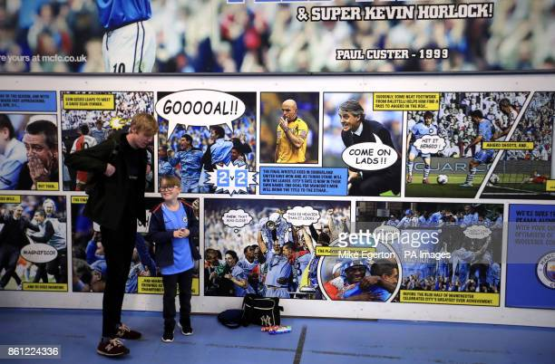Manchester City fans in front of a comic book inspired photo board inside the ground before the Premier League match at Etihad Stadium Manchester