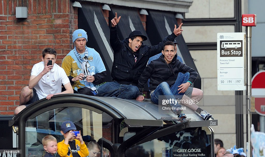Manchester City fans look on from the top of a bus shelter during the victory parade around the streets of Manchester on May 14, 2012 in Manchester, United Kingdom.