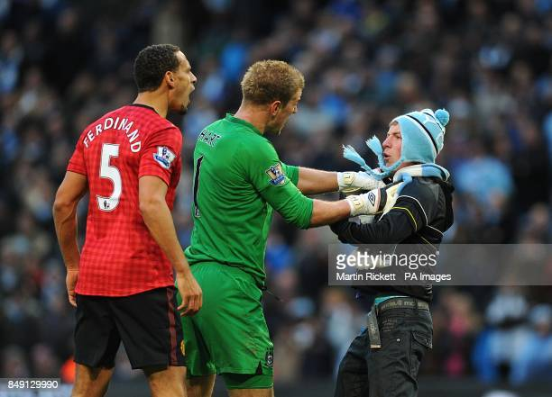 Manchester City goalkeeper Joe Hart holds back a fan as he goes towards Manchester United's Rio Ferdinand who was struck by an object thrown from the...