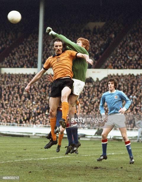 Manchester City goalkeeper Keith MacRae punches clear from the head of Wolves striker Derek Dougan during the 1974 League Cup Final between...