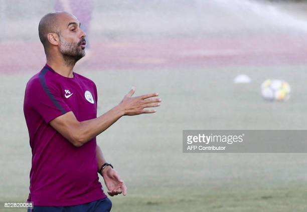 Manchester City head coach Pep Guardiola speaks to players during in a training session at the StubHub Center on July 25 2017 in Carson California /...