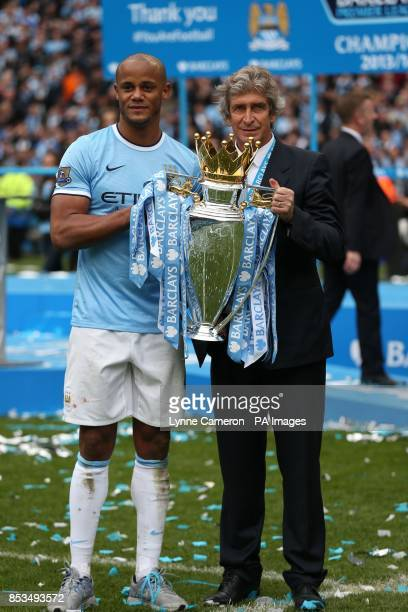 Manchester City manager Manuel Pellegrini and Vincent Kompany hold the Premier League Trophy after the Barclays Premier League match at the Etihad...