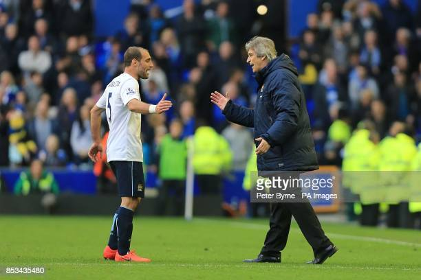 Manchester City manager Manuel Pellegrini celebrates with Pablo Zabaleta after the final whistle