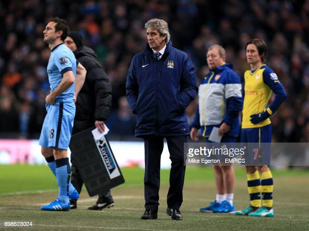 Manchester City manager Manuel Pellegrini looks on as Arsenal's Tomas Rosicky and Manchester City's Frank Lampard wait to come on as substitutes