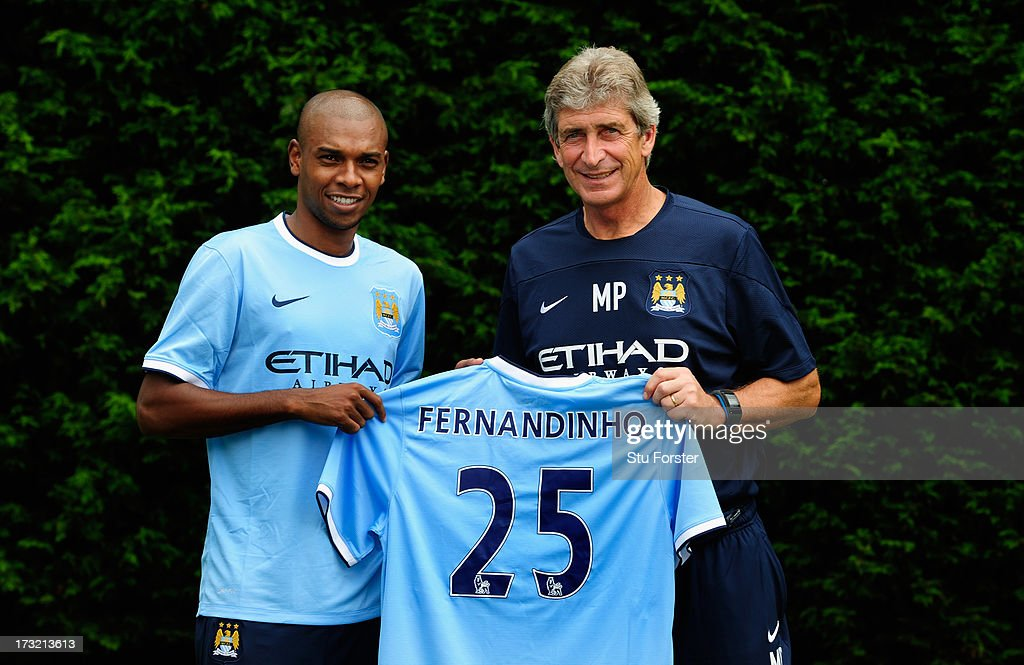 Manchester City manager Manuel Pellegrini poses with a team shirt with new player Fernandinho after their first media conference at Carrington Training Ground on July 10, 2013 in Manchester, England.