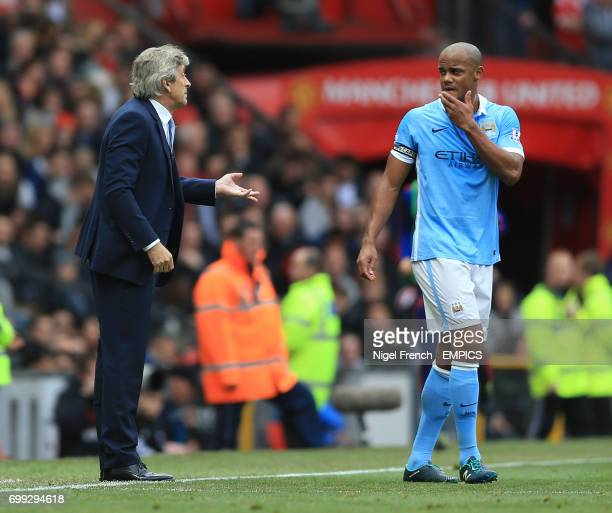 Manchester City manager Manuel Pellegrini talks to his captain Vincent Kompany during the game against Manchester United