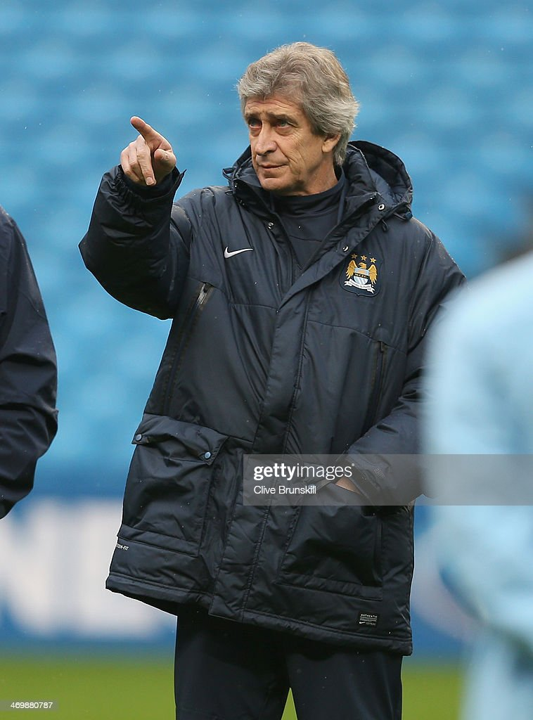Manchester City manager <a gi-track='captionPersonalityLinkClicked' href=/galleries/search?phrase=Manuel+Pellegrini&family=editorial&specificpeople=673553 ng-click='$event.stopPropagation()'>Manuel Pellegrini</a> with gives instruction during a training session ahead of their UEFA Champions League Round of 16 match 1st leg against Barcelona at Etihad Stadium on February 17, 2014 in Manchester, England.