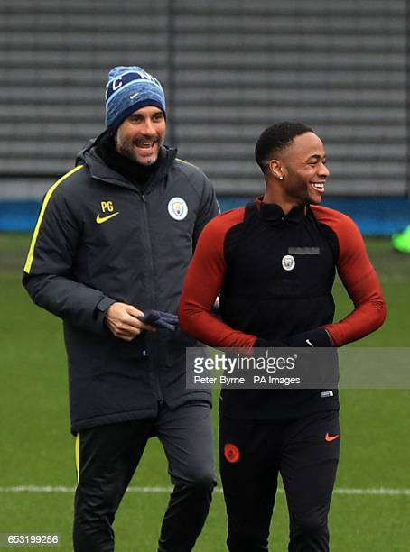 Manchester City manager Pep Guardiola shares a joke with Raheem Sterling during the training session at the City Football Academy Manchester