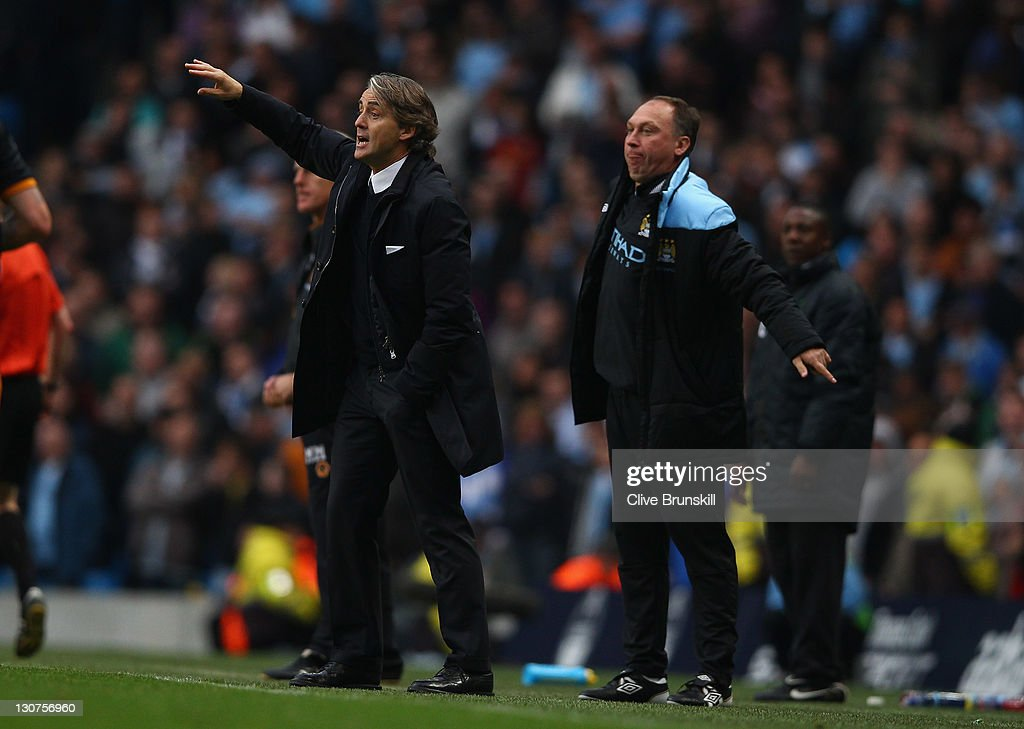 Manchester City manager <a gi-track='captionPersonalityLinkClicked' href=/galleries/search?phrase=Roberto+Mancini&family=editorial&specificpeople=234429 ng-click='$event.stopPropagation()'>Roberto Mancini</a> gives instructions watched by <a gi-track='captionPersonalityLinkClicked' href=/galleries/search?phrase=David+Platt&family=editorial&specificpeople=2115828 ng-click='$event.stopPropagation()'>David Platt</a> during the Barclays Premier League match between Manchester City and Wolverhampton Wanderers at Etihad Stadium on October 29, 2011 in Manchester, England.
