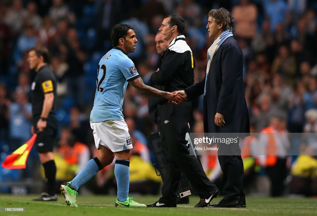 Manchester City Manager <a gi-track='captionPersonalityLinkClicked' href=/galleries/search?phrase=Roberto+Mancini&family=editorial&specificpeople=234429 ng-click='$event.stopPropagation()'>Roberto Mancini</a> shakes hands with <a gi-track='captionPersonalityLinkClicked' href=/galleries/search?phrase=Carlos+Tevez&family=editorial&specificpeople=220555 ng-click='$event.stopPropagation()'>Carlos Tevez</a> as he is substituted during the Barclays Premier League match between Manchester City and West Bromwich Albion at the Etihad Stadium on May 07, 2013 in Manchester, England.