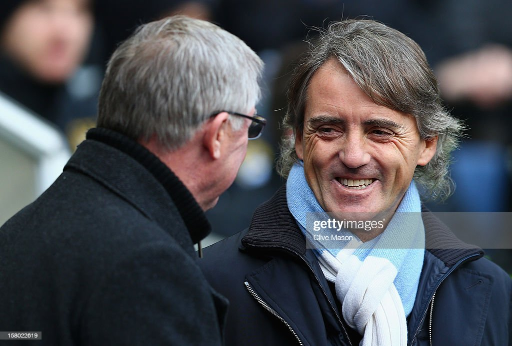 Manchester City Manager Roberto Mancini shares a joke with Manchester United Manager Sir Alex Ferguson (L) prior to the Barclays Premier League match between Manchester City and Manchester United at the Etihad Stadium on December 9, 2012 in Manchester, England.