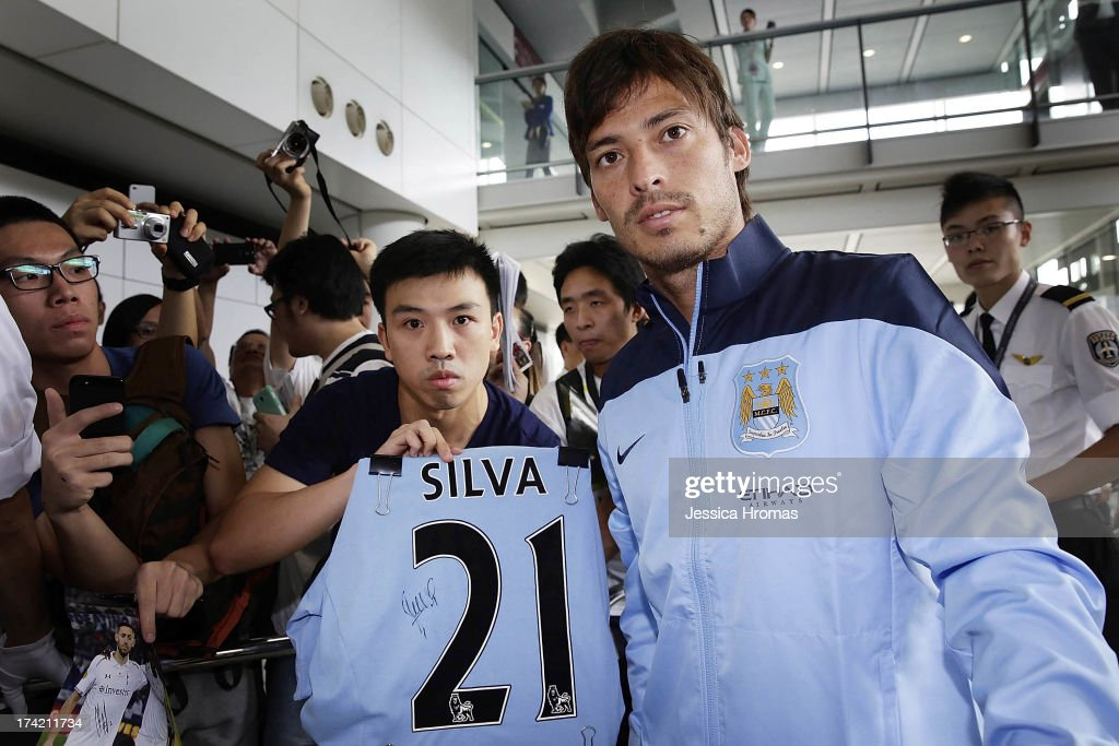 Manchester City player <a gi-track='captionPersonalityLinkClicked' href=/galleries/search?phrase=David+Silva&family=editorial&specificpeople=675795 ng-click='$event.stopPropagation()'>David Silva</a> poses for a photo with a fan at Hong Kong Airport as they arrive to compete in the Barclays Asia Trophy, on July 22, 2013 in Hong Kong.