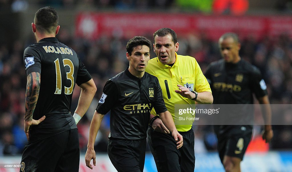 Manchester City player Jesus Navas is spoken to by referee Phil Dowd during the Barclays Premier League match between Swansea City and Manchester City at Liberty Stadium on January 1, 2014 in Swansea, Wales.