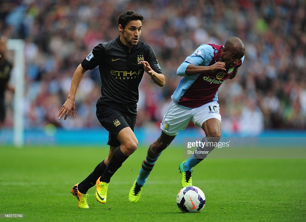 Manchester City player Jesus Navas (l) outpaces Fabian Delph of Villa during the Barclays Premier League match between Aston Villa and Manchester City at Villa Park on September 28, 2013 in Birmingham, England.