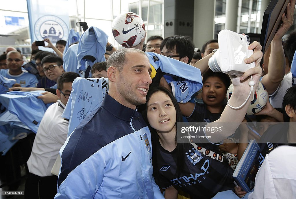 Manchester City player Pablo Zabaletaf poses for a photo with a Manchester City fan at Hong Kong Airport shortly after the team arrives to compete in the Barclays Asia Trophy, on July 22, 2013 in Hong Kong.