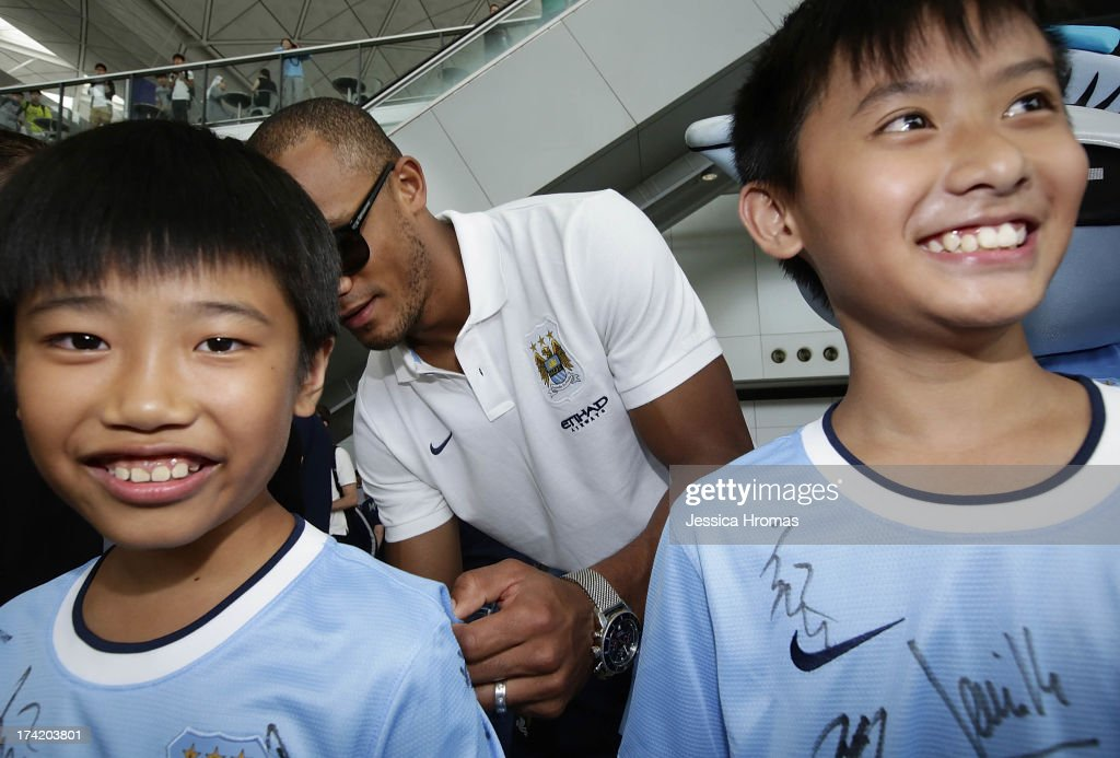 Manchester City team captain <a gi-track='captionPersonalityLinkClicked' href=/galleries/search?phrase=Vincent+Kompany&family=editorial&specificpeople=504694 ng-click='$event.stopPropagation()'>Vincent Kompany</a> (C) signs autographs for Edison Lai and Andrew Lo at Hong Kong Airport after the team arrives to compete in the Barclays Asia Trophy, on July 22, 2013 in Hong Kong.