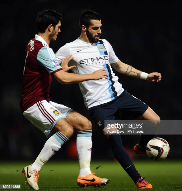 Manchester City's Alvaro Negredo and West Ham United's James Tomkins battle for the ball during the Capital One Cup Semi Final Second Leg match at...