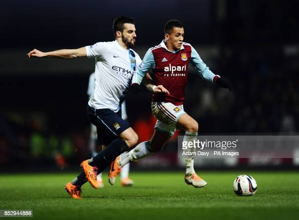 Manchester City's Alvaro Negredo and West Ham United's Ravel Morrison battle for the ball during the Capital One Cup Semi Final Second Leg match at...