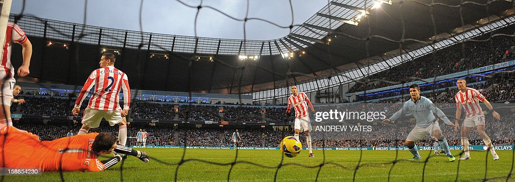 """Manchester City's Argentian defender Pablo Zabaleta (2nd L hidden) scores the opening goal past Stoke City's Bosnian goalkeeper Asmir Begovic (L) during the English Premier League football match between Manchester City and Stoke City at The Etihad stadium in Manchester, north-west England on January 1, 2013. USE. No use with unauthorized audio, video, data, fixture lists, club/league logos or """"live"""" services. Online in-match use limited to 45 images, no video emulation. No use in betting, games or single club/league/player publications."""