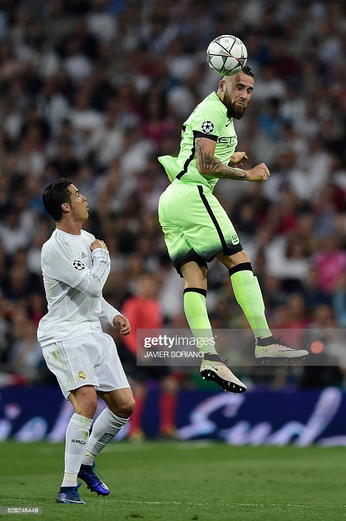 Manchester City's Argentinian defender Nicolas Otamendi (R) heads the ball past Real Madrid's Portuguese forward Cristiano Ronaldo during the UEFA Champions League semi-final second leg football match Real Madrid CF vs Manchester City FC at the Santiago Bernabeu stadium in Madrid, on May 4, 2016. / AFP / JAVIER