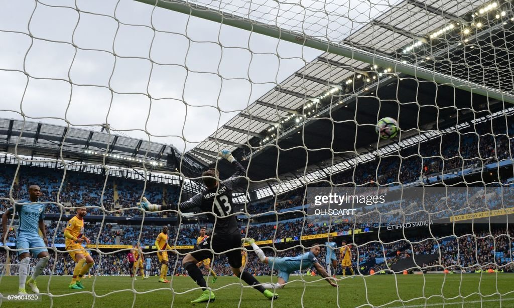Manchester City's Argentinian defender Nicolas Otamendi (centre R) watches the ball after heading to score his team's fifth goal during the English Premier League football match between Manchester City and Crystal Palace at the Etihad Stadium in Manchester, north west England, on May 6, 2017. Manchester City won the match 5-0. / AFP PHOTO / Oli SCARFF / RESTRICTED TO EDITORIAL USE. No use with unauthorized audio, video, data, fixture lists, club/league logos or 'live' services. Online in-match use limited to 75 images, no video emulation. No use in betting, games or single club/league/player publications. /