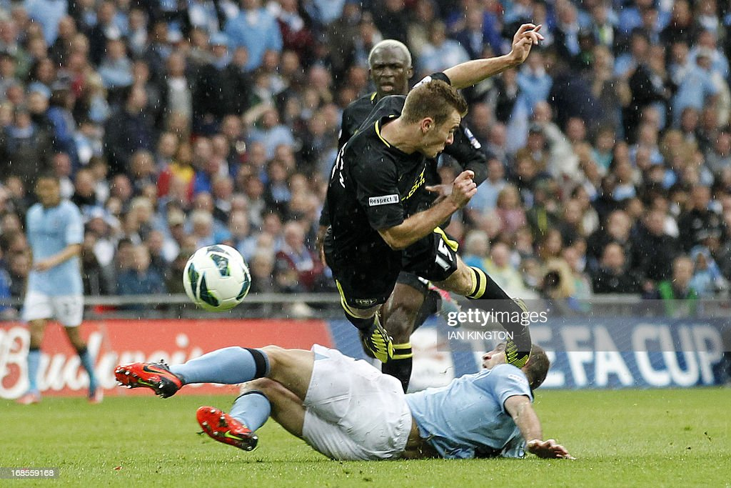 Manchester City's Argentinian defender Pablo Zabaleta (floor) brings down Wigan Athletic's English striker Callum McManaman (top) in a challenge that earned him his second yellow card to see him sent off during the English FA Cup final football match between Manchester City and Wigan Athletic at Wembley Stadium in London on May 11, 2013. AFP PHOTO / IAN KINGTON USE