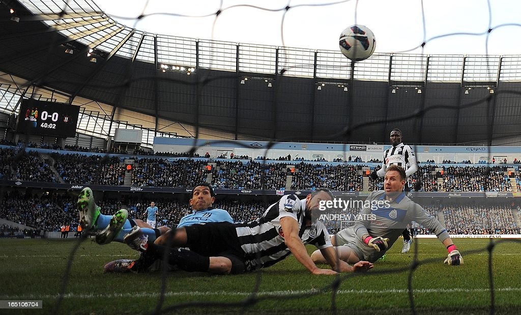 "Manchester City's Argentinian forward Carlos Tevez (L) scores the opening goal during the English Premier League football match between Manchester City and Newcastle United at The Etihad stadium in Manchester, north-west England on March 30, 2013. USE. No use with unauthorized audio, video, data, fixture lists, club/league logos or ""live"" services. Online in-match use limited to 45 images, no video emulation. No use in betting, games or single club/league/player publications. """