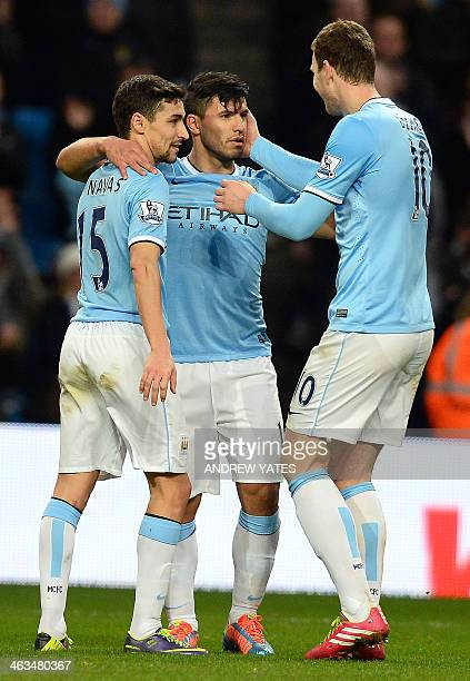 Manchester City's Argentinian forward Sergio Aguero celebrates with Spanish midfielder Jesus Navas and Bosnian forward Edin Dzeko after scoring his...