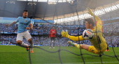 Manchester City's Argentinian forward Sergio Aguero scores his teams third goal past Manchester United's Spanish goalkeeper David de Gea during the...