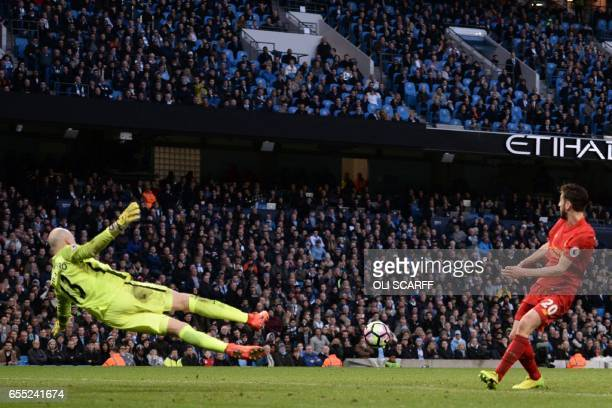 Manchester CIty's Argentinian goalkeeper Willy Caballero dives but Liverpool's English midfielder Adam Lallana manages to miss his shot during the...