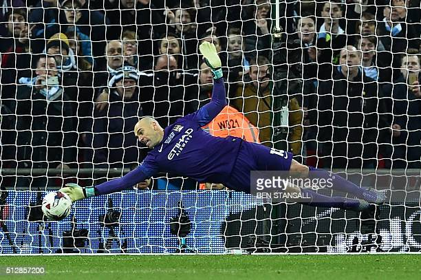 Manchester CIty's Argentinian goalkeeper Willy Caballero saves the penalty from Liverpool's English midfielder Adam Lallana during the penalty...
