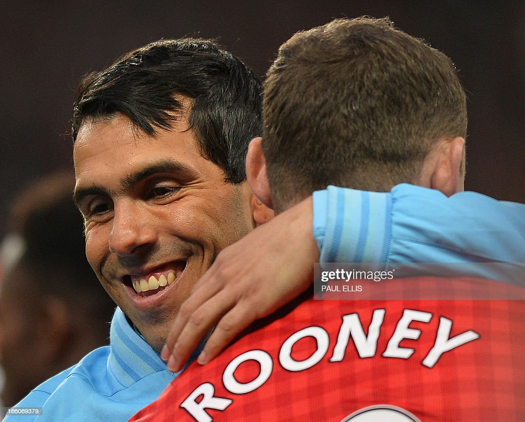 "Manchester City's Argentinian striker Carlos Tevez (L) greets Manchester United's English striker Wayne Rooney (R) before the English Premier League football match between Manchester United and Manchester City at Old Trafford in Manchester, northwest England on April 8, 2013. AFP/PHOTO PAUL ELLIS USE. No use with unauthorized audio, video, data, fixture lists, club/league logos or ""live"" services. Online in-match use limited to 45 images, no video emulation. No use in betting, games or single club/league/player publications."