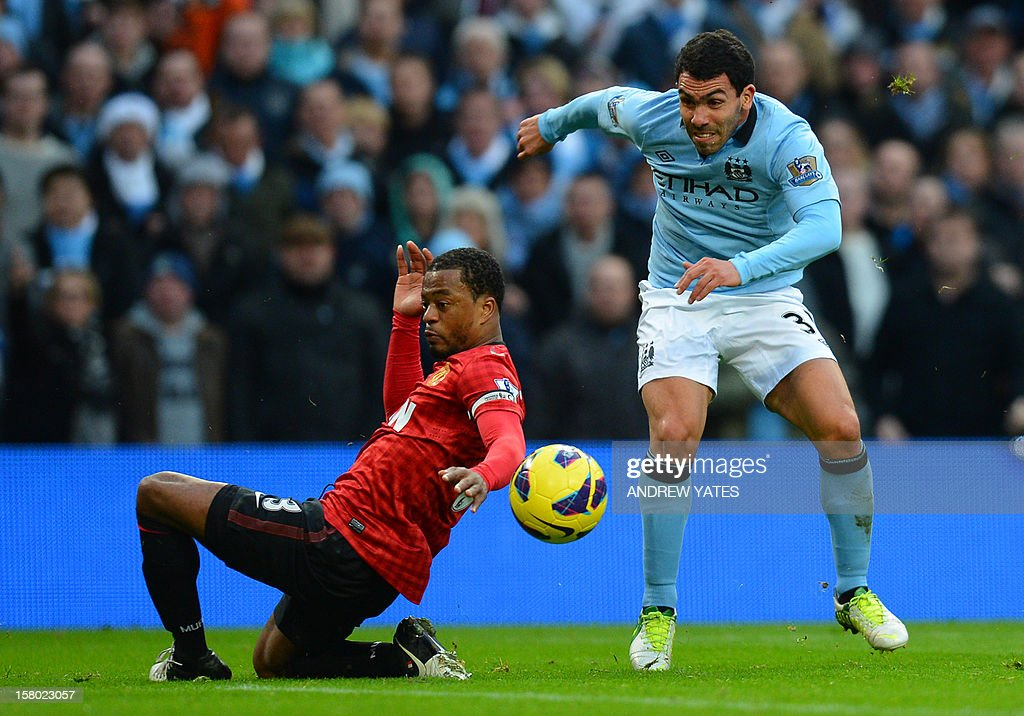 """Manchester City's Argentinian striker Carlos Tevez (R) shoots past Manchester United's French defender Patrice Evra (L) during the English Premier League football match between Manchester City and Manchester United at The Etihad stadium in Manchester, north-west England on December 9, 2012. USE. No use with unauthorized audio, video, data, fixture lists, club/league logos or """"live"""" services. Online in-match use limited to 45 images, no video emulation. No use in betting, games or single club/league/player publications."""