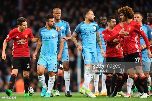 Manchester City's Argentinian striker Sergio Aguero and Manchester United's Belgian midfielder Marouane Fellaini are seperated by teammates in an...