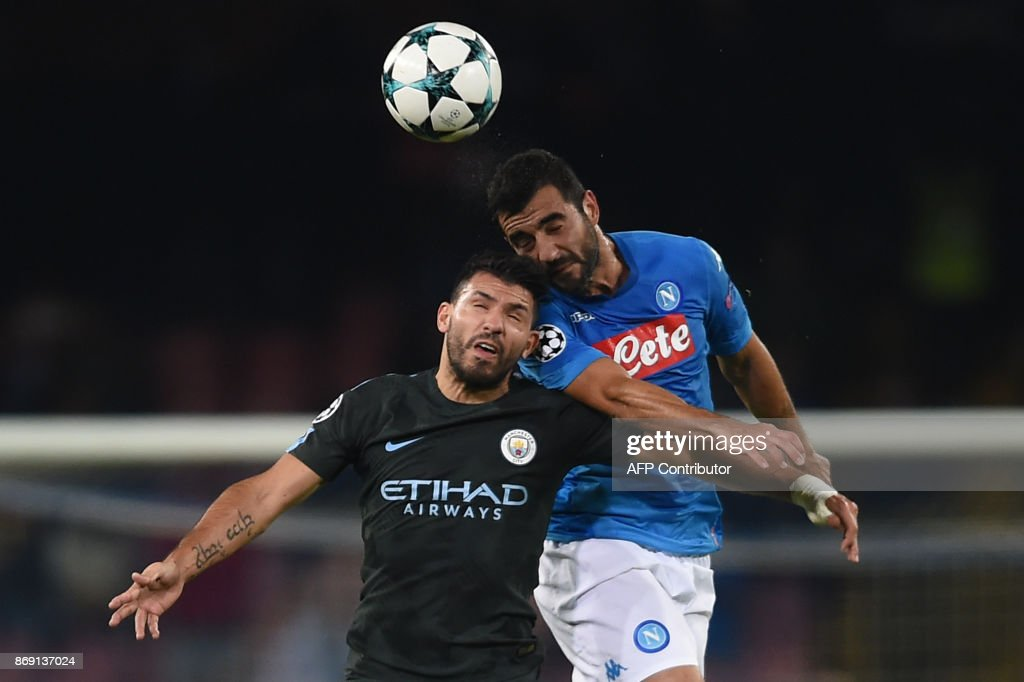 Manchester City's Argentinian striker Sergio Aguero (L) and Napoli's defender from Spain Raul Albiol jump for the ball during the UEFA Champions League football match Napoli vs Manchester City on November 1, 2017 at the San Paolo stadium in Naples. Manchester City won 2-4. / AFP PHOTO / Filippo MONTEFORTE