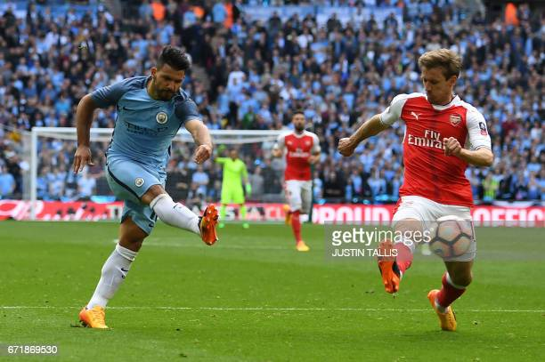 Manchester City's Argentinian striker Sergio Aguero attempts a shot at goal past Arsenal's Spanish defender Nacho Monreal during the FA Cup semifinal...