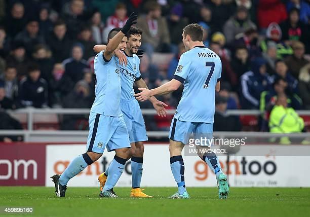 Manchester City's Argentinian striker Sergio Aguero celebrates scoring his second goal with Manchester City's Spanish midfielder Jesus Navas and...