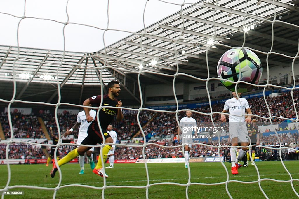 Manchester City's Argentinian striker Sergio Aguero (L) celebrates scoring their second goal from the penalty spot during the English Premier League football match between Swansea City and Manchester City at The Liberty Stadium in Swansea, south Wales on September 24, 2016. / AFP / Adrian DENNIS / RESTRICTED TO EDITORIAL USE. No use with unauthorized audio, video, data, fixture lists, club/league logos or 'live' services. Online in-match use limited to 75 images, no video emulation. No use in betting, games or single club/league/player publications. /