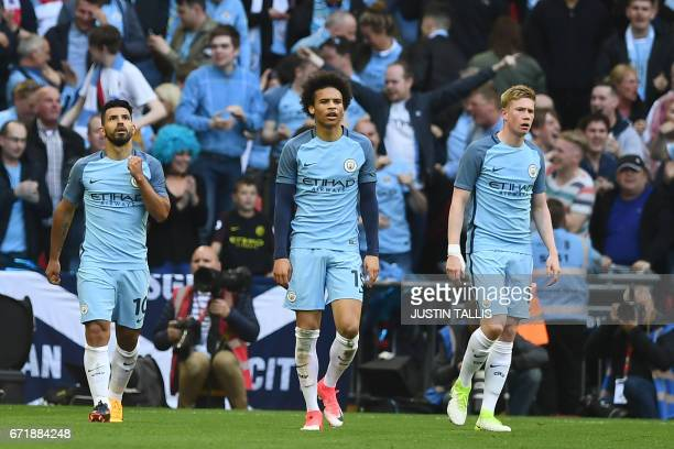 Manchester City's Argentinian striker Sergio Aguero celebrates scoring the opening goal with Manchester City's German midfielder Leroy Sane and...