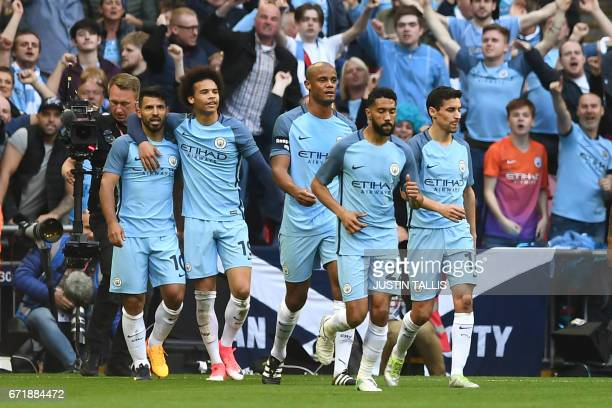 Manchester City's Argentinian striker Sergio Aguero celebrates scoring the opening goal with Manchester City's German midfielder Leroy Sane during...