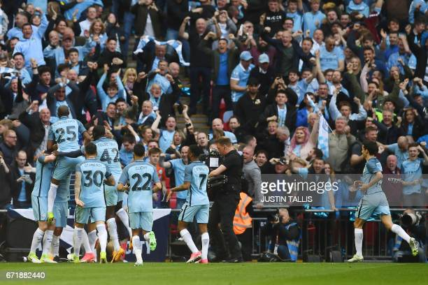 Manchester City's Argentinian striker Sergio Aguero celebrates with teammates scoring the opening goal during the FA Cup semifinal football match...