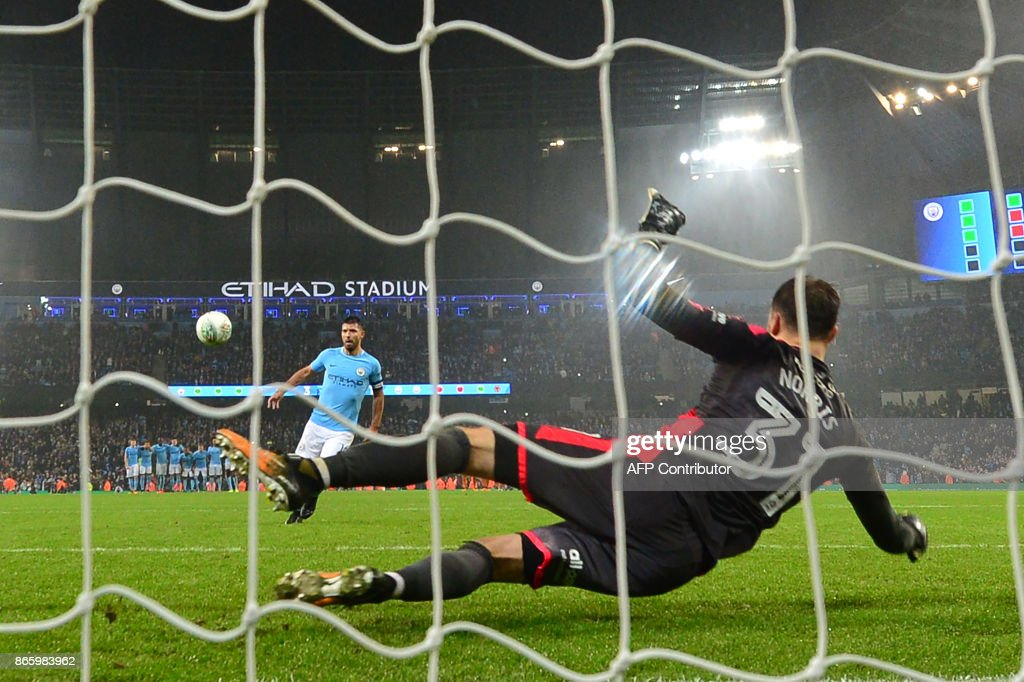 Manchester City's Argentinian striker Sergio Aguero (L) chips the ball over Wolverhampton Wanderers' English goalkeeper Will Norris (R) to score the winning penalty in the shoot-out during the English League Cup fourth round football match between Manchester City and Wolverhampton Wanderers at the Etihad Stadium in Manchester, north west England, on October 24, 2017. The game ended 0-0 after extra time. Manchester City won 4-1 on penalties. / AFP PHOTO / Anthony DEVLIN / RESTRICTED TO EDITORIAL USE. No use with unauthorized audio, video, data, fixture lists, club/league logos or 'live' services. Online in-match use limited to 75 images, no video emulation. No use in betting, games or single club/league/player publications. /